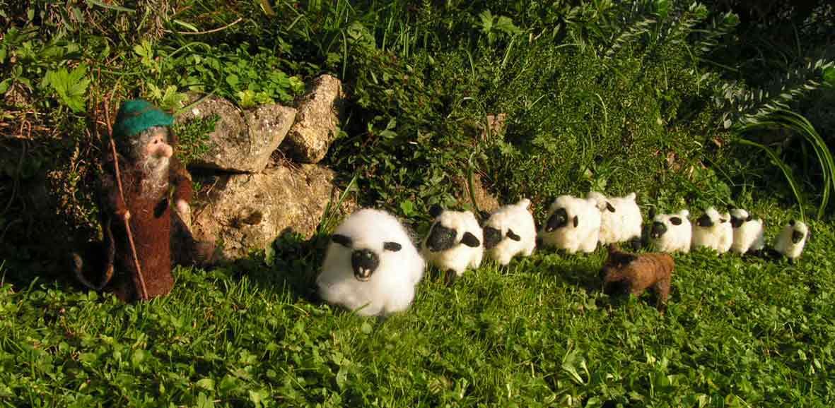 Der urige Filzschäfer mit Wanderstab steht an Steinen und wartet auf seine Schafe, die im grünen Gras in einer langen Reihe hinter Emma, dem Schaf stehen